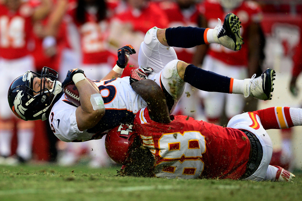 . Wes Welker (83) of the Denver Broncos gets tackled by Junior Hemingway (88) of the Kansas City Chiefs during the first half of action at Arrowhead Stadium.  (Photo by AAron Ontiveroz/The Denver Post)
