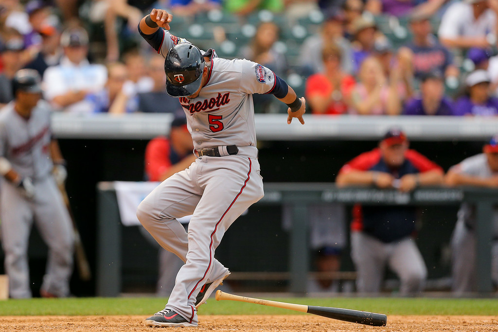 . Eduardo Escobar #5 of the Minnesota Twins trips on a bat as he scores during the ninth inning against the Colorado Rockies at Coors Field on July 13, 2014 in Denver, Colorado. The Twins defeated the Rockies 13-5. (Photo by Justin Edmonds/Getty Images)