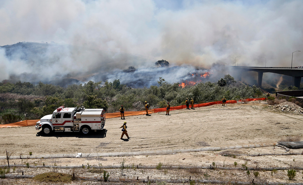 . Firefighters battle a wild fire in the Santa Luz area of San Diego Tuesday, May 13, 2014.  (AP Photo)