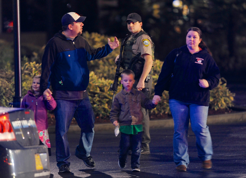 . A family leaves the scene of a multiple shooting at Clackamas Town Center Mall in Clackamas, Ore., Tuesday Dec. 11, 2012. A gunman is dead after opening fire in the Portland, Ore., area shopping mall Tuesday, killing two people and wounding another, sheriff\'s deputies said. (AP Photo/Greg Wahl-Stephens)