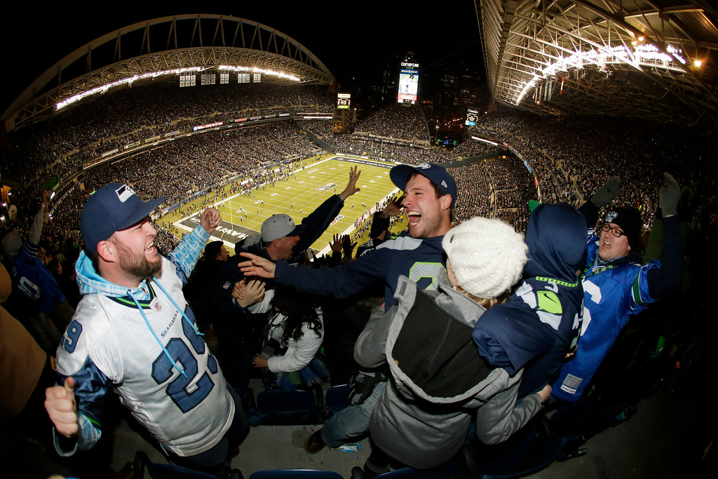 . Seattle Seahawks fans celebrate after Seahawks\' Michael Bennett recovered a New Orleans Saints fumble and scored a touchdown in the first half of an NFL football game, Monday, Dec. 2, 2013, in Seattle. (AP Photo/John Froschauer)