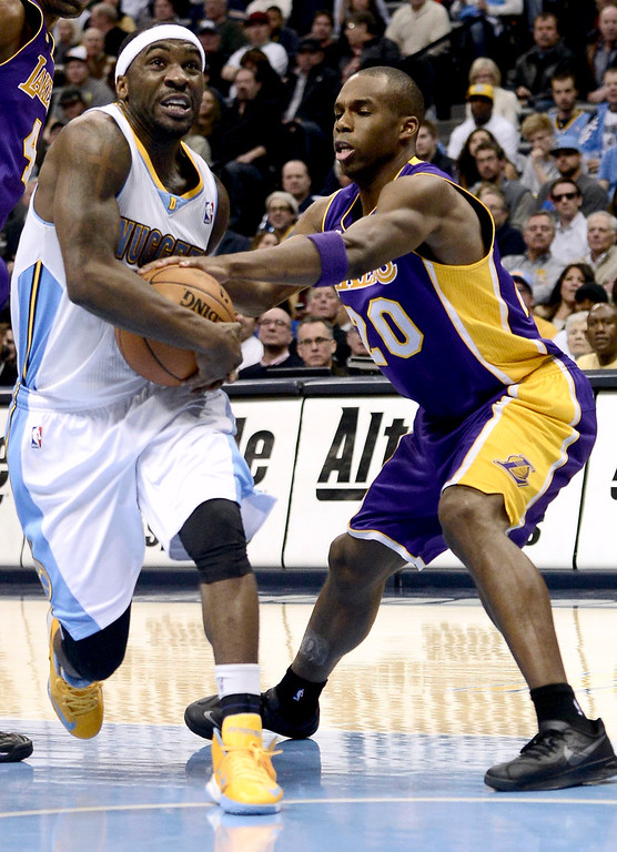 . Denver Nuggets\' Ty Lawson (L) is fouled by Los Angeles Lakers\' Jodie Meeks during their NBA basketball game in Denver, Colorado February 25, 2013.   REUTERS/Mark Leffingwell