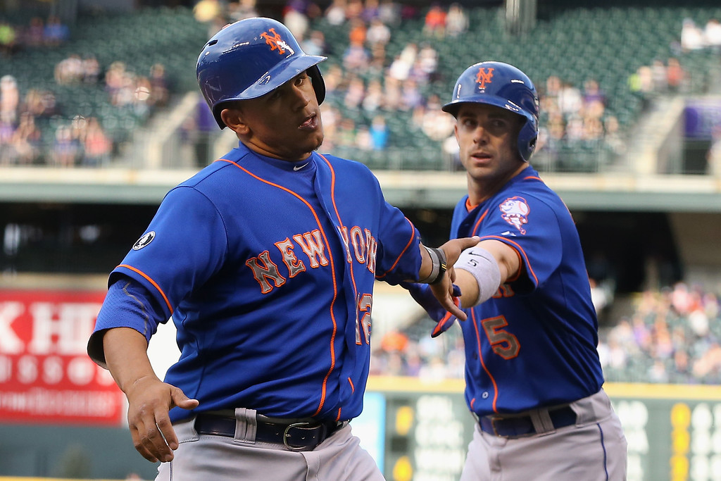 . DENVER, CO - MAY 02:  Juan Lagares #12 of the New York Mets scoress on a wild pitch by starting pitcher Jorge De La Rosa #29 of the Colorado Rockies and is congratulated by David Wright #5 of the New York Mets as the Mets took a 1-0 lead in the first inning at Coors Field on May 2, 2014 in Denver, Colorado.  (Photo by Doug Pensinger/Getty Images)