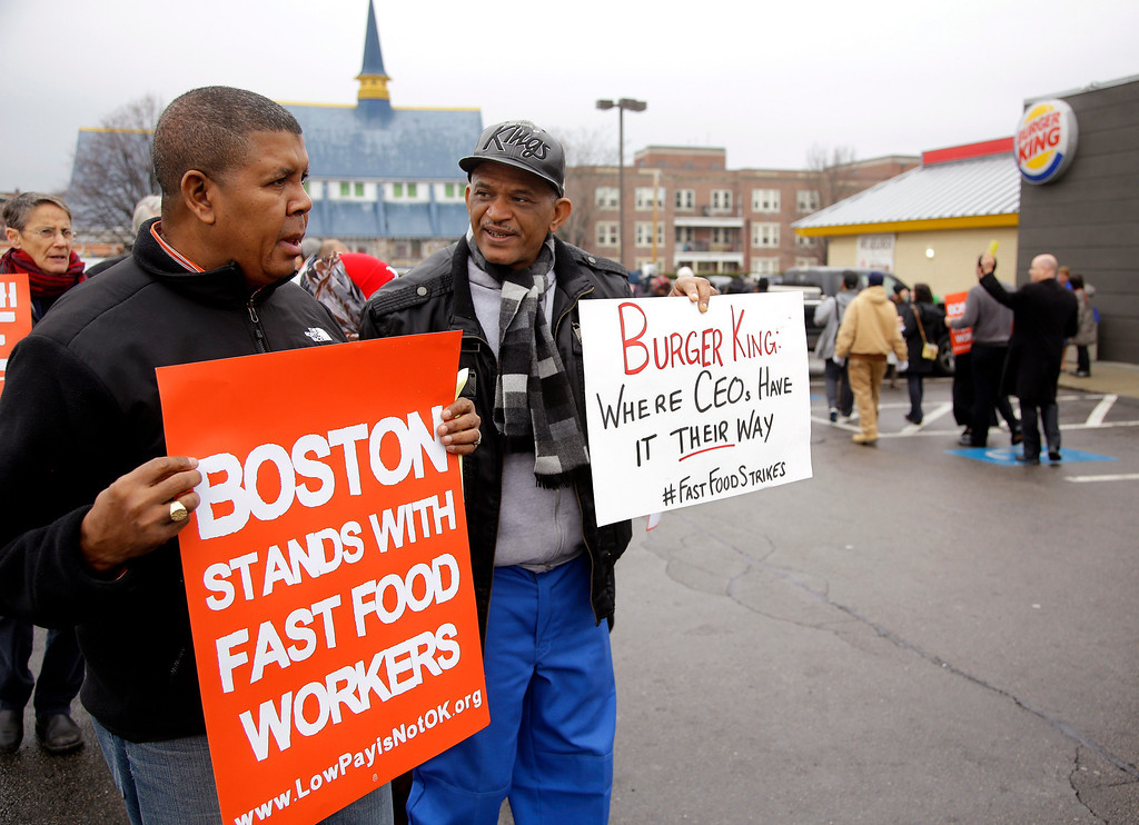 ". Pedro Rodriguez, right, talks with Andrus Reyes as they participate in a demonstration on a Burger King parking lot as part of a nationwide protest supporting higher wages for workers in the fast-food industry and other minimum wage jobs in Boston, Thursday, Dec. 5, 2013. Rodriguez was once an employee of this Burger King restaurant before being ""let go\"" and Reyes  works for Local 32 VJ, the union who represents workers hired to clean the restaurant they are protesting. (AP Photo/Stephan Savoia)"