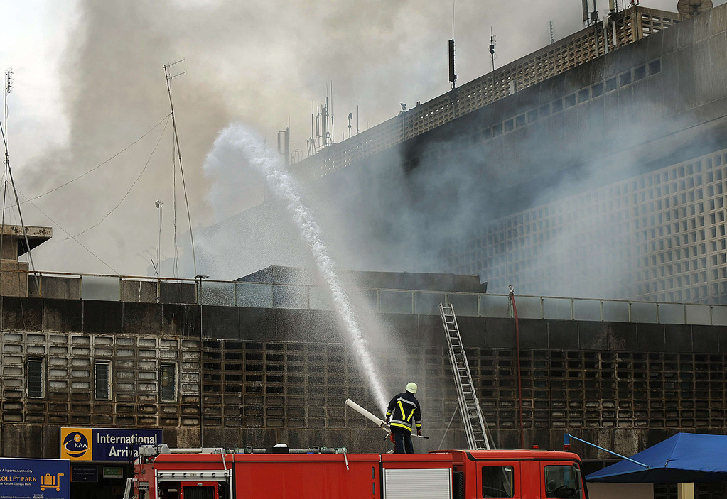 . A fire fighter shoots a water canon at the still smouldering building that houses the international arrivals area that was gutted by an inferno at the Jomo Kenyatta International airport in Nairobi on August 7, 2013.   AFP PHOTO / Tony KARUMBA/AFP/Getty Images