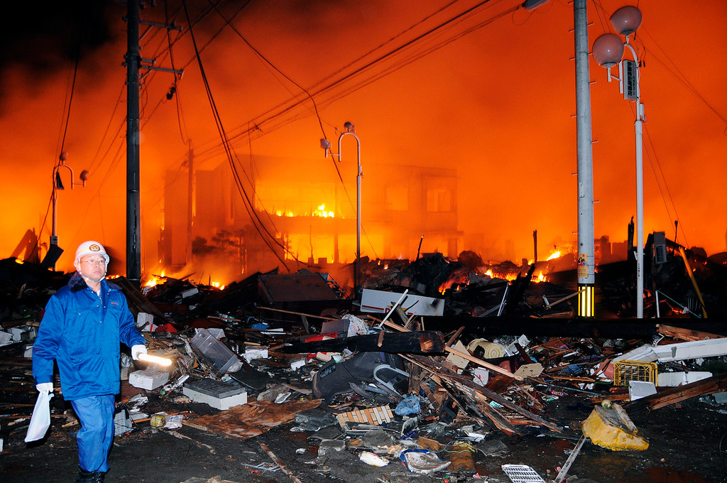 . A helmeted man walks past the rubbles and a burning building after a powerful earthquake, the largest in Japan\'s recorded history, slammed the eastern coasts in Iwaki city, Fukushima prefecture, Japan, Friday, March 11, 2011. (AP Photo/Kyodo News)