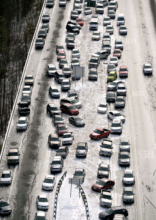 . In this aerial photo, abandoned cars at I-75 headed northbound near the Chattahoochee River overpass are piled up in the median of the ice-covered interstate after a winter snow storm , Wednesday, Jan. 29, 2014, in Atlanta. Georgia Gov. Nathan Deal said early Wednesday that the National Guard was sending military Humvees onto Atlanta\'s snarled freeway system in an attempt to move stranded school buses and get food and water to people. Georgia State Patrol troopers headed to schools where children were hunkered down early Wednesday after spending the night there, and transportation crews continued to treat roads and bring gas to motorists, Deal said.  (AP Photo/David Tulis)