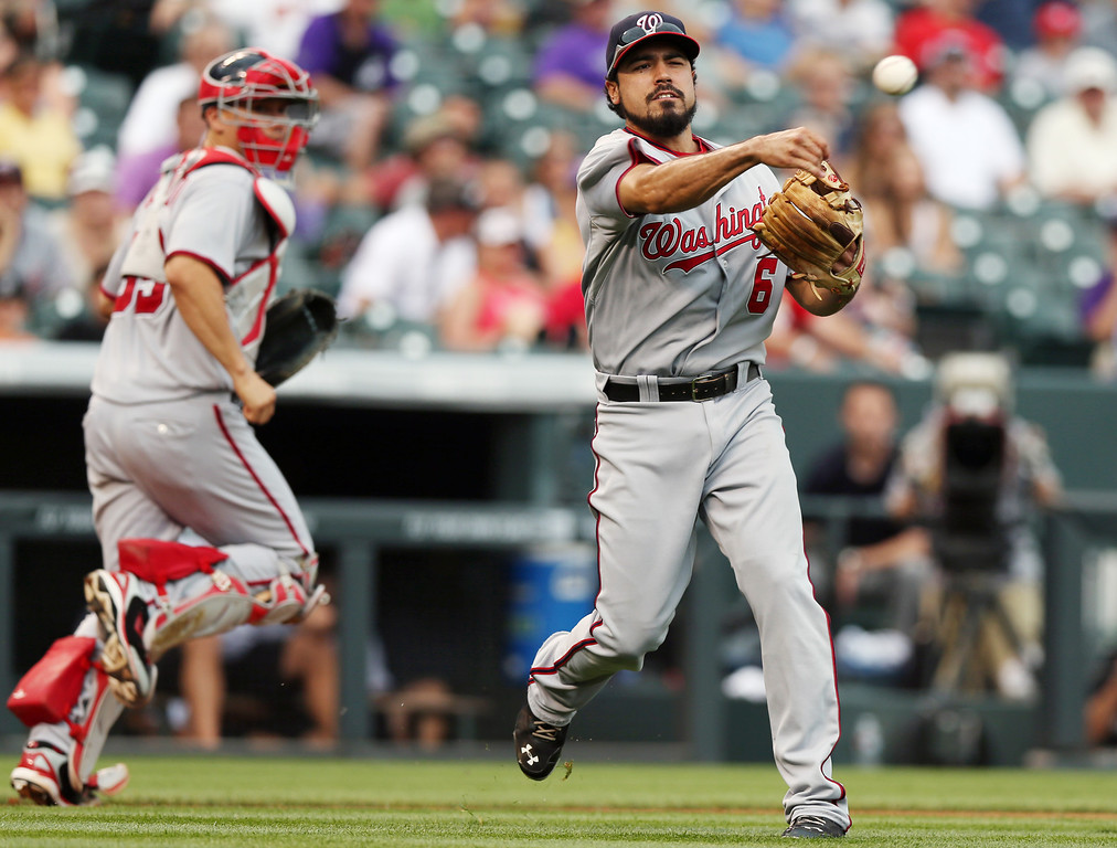. Washington Nationals thid baseman Anthony Rendon, front, throws to first base to put out Colorado Rockies\' Jorge De La Rosa as Nationals catcher Jose Lobaton covers in the fourth inning of a baseball game in Denver on Wednesday, July 23, 2014. (AP Photo)