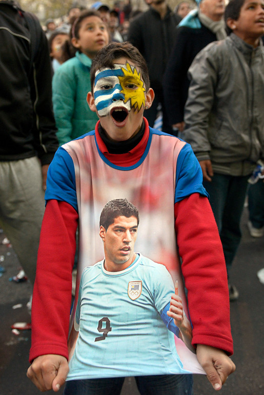 . A soccer fan, with his face painted to represent his country\'s flag and wearing a T-shirt with an image of Uruguayan footballer Luis Suarez, cheers as he watches a live broadcast of the World Cup match between England and Uruguay in downtown Montevideo, Uruguay, Thursday, June 19, 2014. Suarez scored twice to give Uruguay a 2-1 victory over England, making an instant impact on his return from injury to revive his team\'s Group D campaign. (AP Photo/Matilde Campodonico)