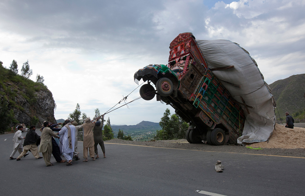 . Men use ropes to try and right a supply truck overloaded with wheat straw, used as animal feed, along a road in Dargai, in the Malakand district, about 165 km (100 miles) northwest of Pakistan\'s capital Islamabad, April 13, 2012. REUTERS/Mian Khursheed