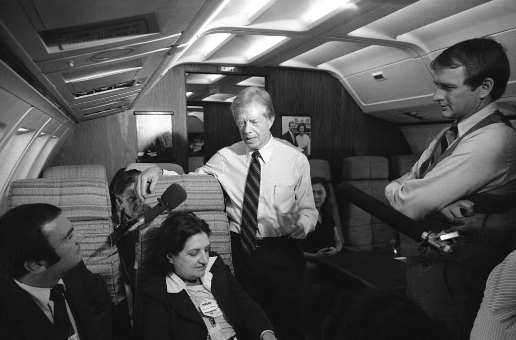. President Jimmy Carter and press secretary Jody Powell, right, chat with reporters while standing in the aisle of the presidential aircraft, Air Force One prior to landing at Andrews Air Force Base, Maryland , Oct. 20, 1979. Carter was returning to Washington after attending the dedication of the John F. Kennedy presidential library in Boston. The president said that he enjoyed seeing the library and felt that politically, he is as close to John F. Kennedy as is the late president�s brother, Sen. Edward Kennedy. Reporters seated at left are Sam Donaldson and Helen Thomas. (AP Photo/Charles Tasnadi)