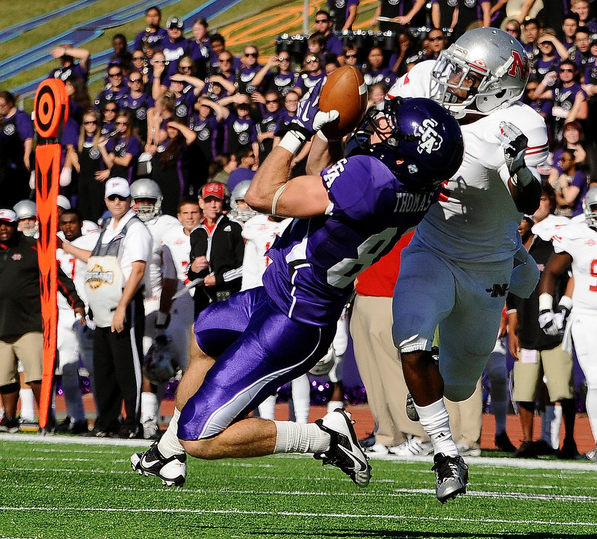 . Stephen F. Austin State wide receiver Aaron Thomas, left, jumps for a reception under pressure from Nicholls State defensive back Ronald Tyler (3) during the first half of an NCAA college football game Saturday, Oct. 19, 2013, in Nacogdoches, Texas. (AP Photo/The Daily Sentinel, Andrew D. Brosig)