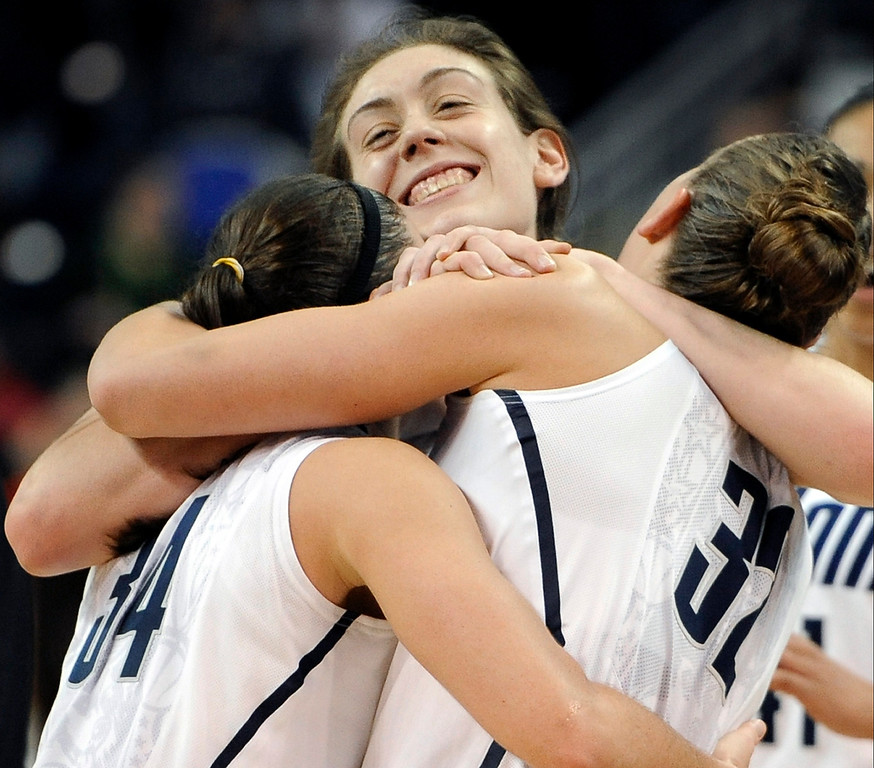 . Connecticut\'s Breanna Stewart, center, embraces teammates Kelly Faris, left, and Heather Buck, right, at the end of a regional final game against Kentucky in the NCAA college basketball tournament in Bridgeport, Conn., Monday, April 1, 2013. Connecticut won 83-53.(AP Photo/Jessica Hill)