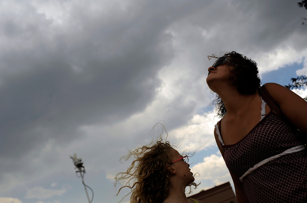 . Chloe, 10, stands by Tiffany Beaubien, right, as she looks up after feeling rain drops at the corner of Garden of Gods Rd. and Centennial Blvd. in Colorado Springs on June 27. Hyoung Chang, The Denver Post