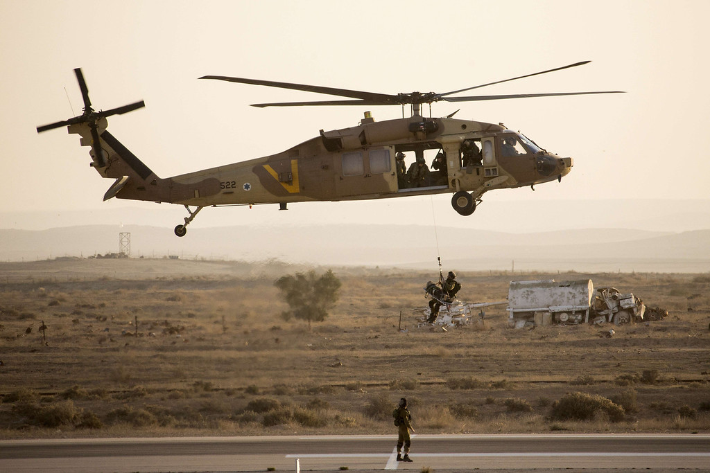 . Israeli air force soldiers display their skills with an UH-60 Black Hawk helicopter during an air show at the graduation ceremony of Israeli air force pilots at the Hatzerim base in the Negev desert, near the southern Israeli city of Beersheva on December 26, 2013. AFP PHOTO/JACK GUEZ/AFP/Getty Images