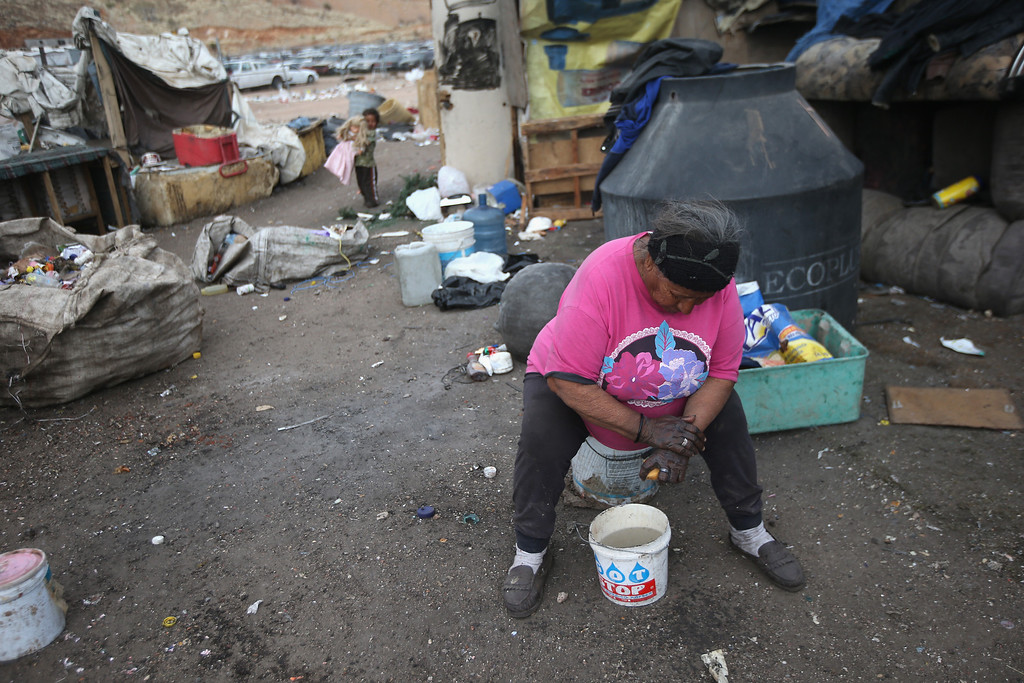 . NOGALES, MEXICO - MARCH 05:  Dona Petra washes her hands in front of her modest home inside the Tirabichi garbage dump on March 5, 2013 in Nogales, Mexico. About 30 families, including Dona Petra, who has worked at the landfill for decades, live at the landfill, searching for recyclables to sell for a living. Many have received aid from the nearby non-profit Home of Hope and Peace, which plans to expand its assistance to Tirabichi residents.  (Photo by John Moore/Getty Images)