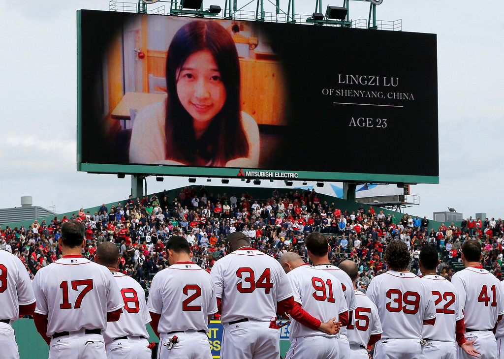 . The Boston Red Sox stand during tribute to Boston Marathon bombing victims, including Chinese student Lingzi Lu, before a baseball game against the Kansas City Royals in Boston, Saturday, April 20, 2013. (AP Photo/Michael Dwyer)