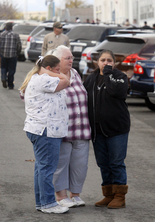 . Unidentified women cry while standing outside Taft Union High School after a shooting on Thursday, Jan. 10, 2012 in Taft, Calif.   The sheriff of Kern County, Calif., says a 16-year-old student shot at a high school is in critical but stable condition. Sheriff Donny Youngblood says the shooter is a student who walked into a class at Taft Union High School Thursday morning and shot the teen with a shotgun, and then fired at another student but missed. A teacher suffered a minor pellet wound to the head. Youngblood says the teacher tried to get other students out a back door, then he and another staff member engaged the shooter in conversation to distract him, and convinced him to put down the gun. (AP Photo/The Bakersfield Californian, Alex Horvath)