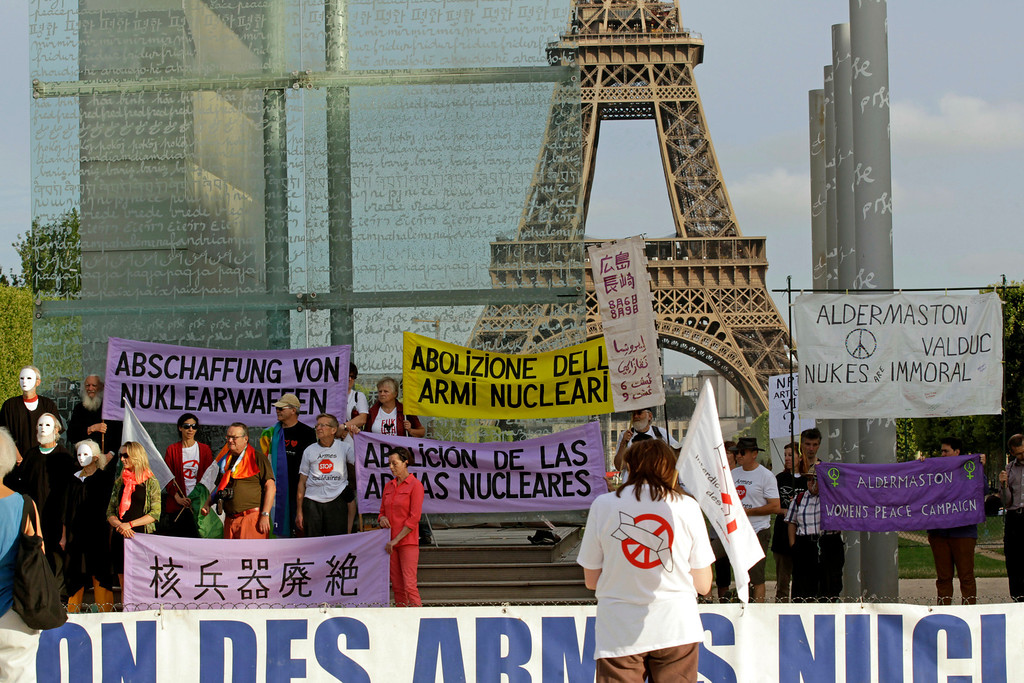 """. Pacifist militants stage a commemorative demonstration at the Peace Wall in Paris, Tuesday Aug. 6, 2013, to mark the 68th anniversary of the atomic bombing of Hiroshima. The signs read \""""Abolition of Nuclear Weapons.\""""  (AP Photo/Remy de la Mauviniere)"""