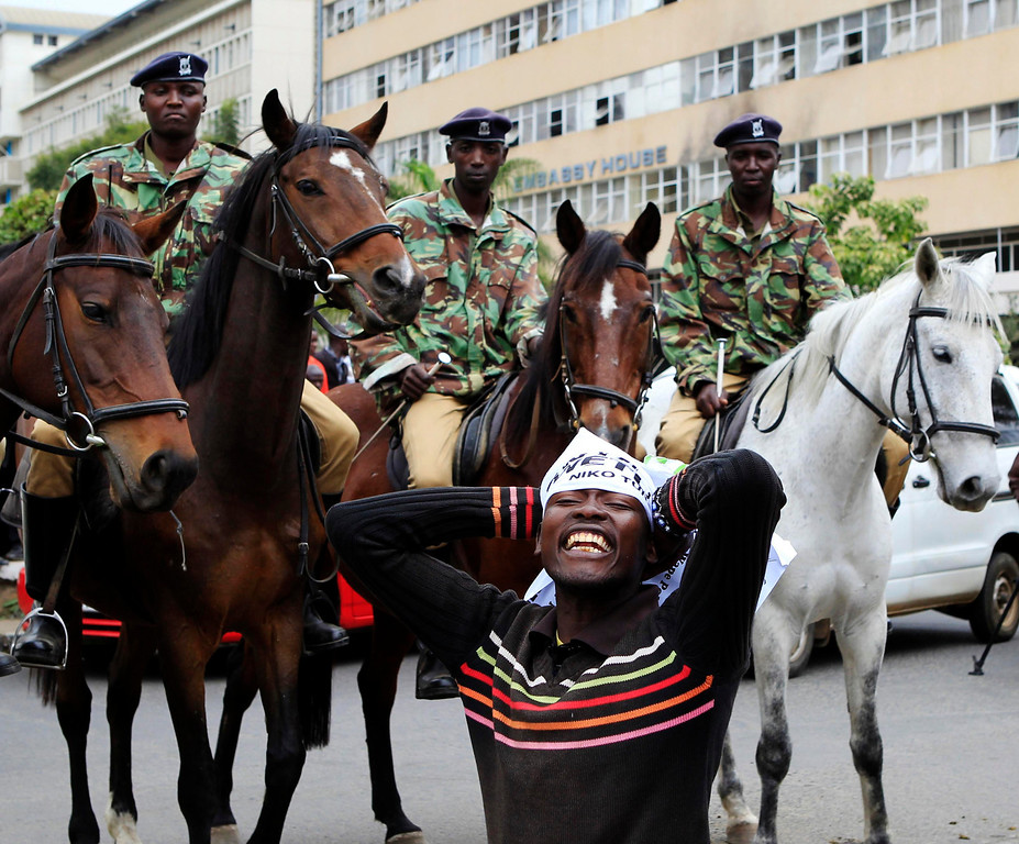 . A protester attends a demonstration against lawmakers\' demands for a pay rise, near police officers mounted on horses, outside parliament buildings in Nairobi, June 11, 2013. Refusing to accept a cut imposed by the Salaries and Remuneration Commission in May, members of parliament voted to increase their salaries to 130 times the minimum wage, which according to them, are needed to deter bribery and provide charitable support for constituents. Protesters have deemed the proposed salary raise a violation of the constitution, according to news reports. REUTERS/Noor Khamis