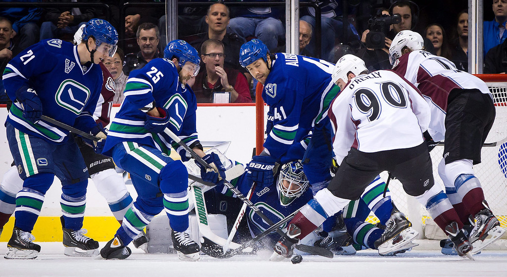 . Vancouver Canucks goalie Cory Schneider, center, follows the puck as teammates, from left to right, Mason Raymond, Andrew Ebbett and Andrew Alberts defend against Colorado Avalanche\'s Ryan O\'Reilly (90) and P.A. Parenteau during the first period of an NHL hockey game in Vancouver, British Columbia, Thursday, March 28, 2013. (AP Phoo/The Canadian Press, Darryl Dyck)