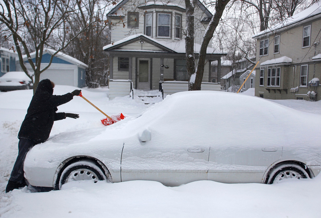 . Jaci Silman uses a snow shovel to clean off her car on Monday, Jan. 27, 2014 in Kalamazoo, Mich.  Temperatures dropped to dangerous, record-breaking lows in Michigan on Tuesday, leading to the closure of hundreds of schools.  (AP Photo/Kalamazoo Gazette-MLive Media Group, Kalamazoo Gazette-MLive Media Group)