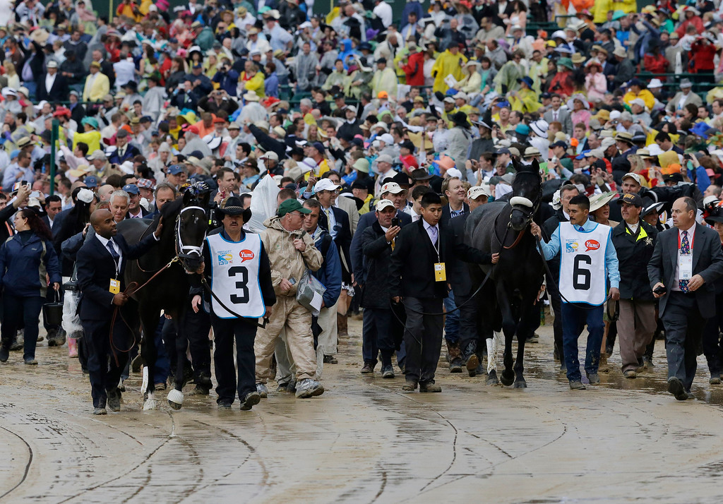 . Grooms walk Derby horses Revolutionary (3) and Mylute (6) to the paddock area before the start of the 139th Kentucky Derby at Churchill Downs Saturday, May 4, 2013, in Louisville, Ky. (AP Photo/J. David Ake)
