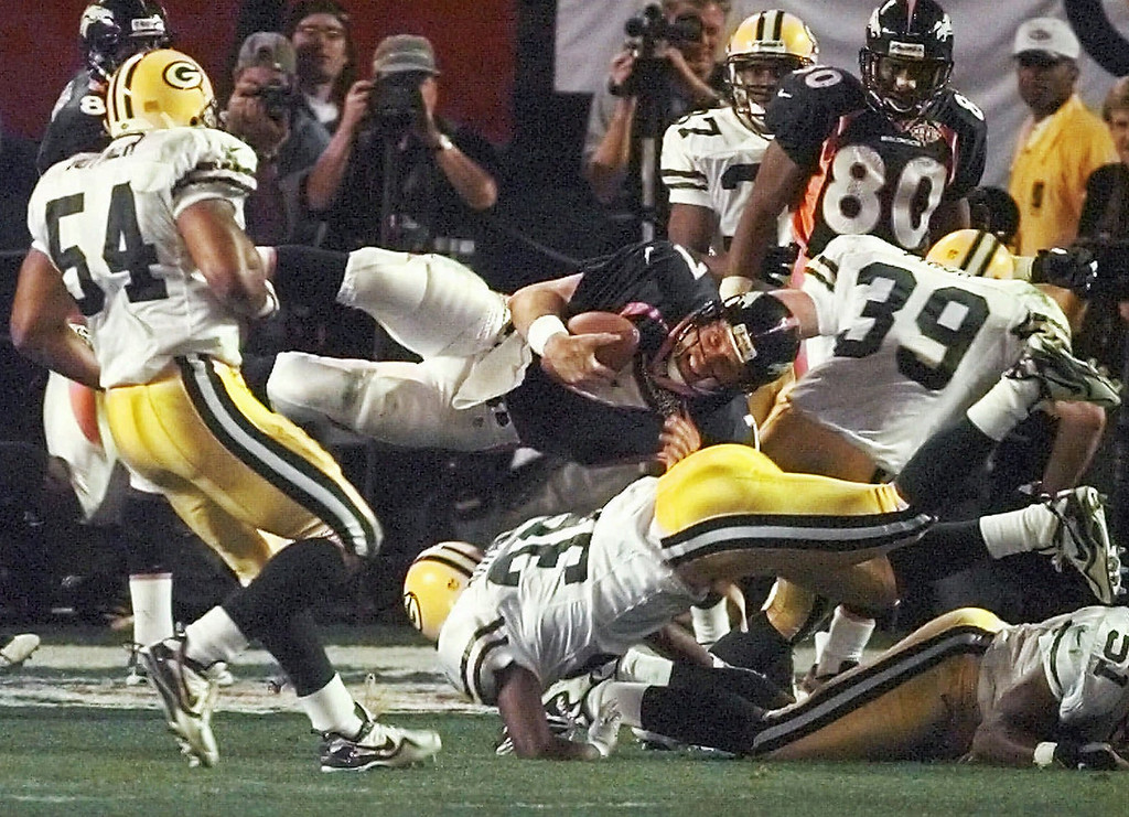 . Denver Broncos quarterback John Elway is upended during the third quarter of Super Bowl XXXII at San Diego\'s Qualcomm Stadium Sunday, Jan. 25, 1998. Green Bay Packers\' Brian Williams (51), Mike Prior (31) and Seth Joyner are in on the play. (AP Photo/Elise Amendola)