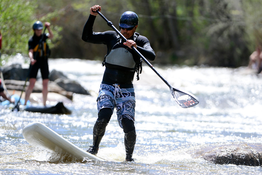 . J.B. Bridenbaugh rides the water en route to winning the paddle board title during Golden Games at the Clear Creek Whitewater Park. (Photo by AAron Ontiveroz/The Denver Post)