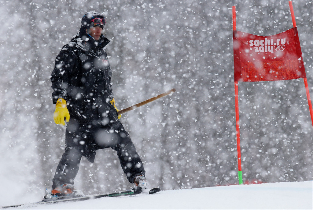 . A ski course worker waits with a shovel under heavy snow fall just before the start of the second run of the women\'s giant slalom at the Sochi 2014 Winter Olympics, Tuesday, Feb. 18, 2014, in Krasnaya Polyana, Russia. (AP Photo/Luca Bruno)