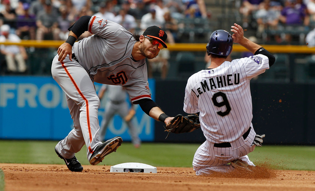 . San Francisco Giants shortstop Brandon Crawford, left, fields a throw as Colorado Rockies\' DJ LeMahieu steals second base in the first inning of a baseball game in Denver on Sunday, June 30, 2013.  (AP Photo/David Zalubowski)