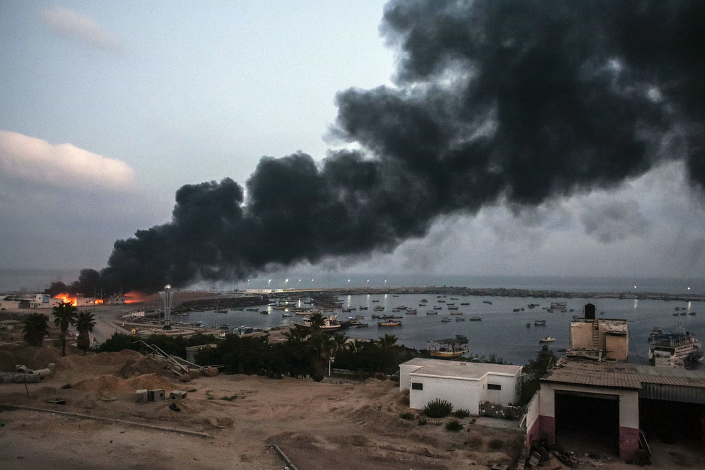 . A building within the Gaza port is seen on fire after several strikes early on July 29, 2014.  Five Israeli soldiers died in clashes with a Palestinian commando that tried to reach Israel through a tunnel at Nahal Oz, near the border with Gaza, the army said.     AFP PHOTO/LOULOU  D\'AKI/AFP/Getty Images