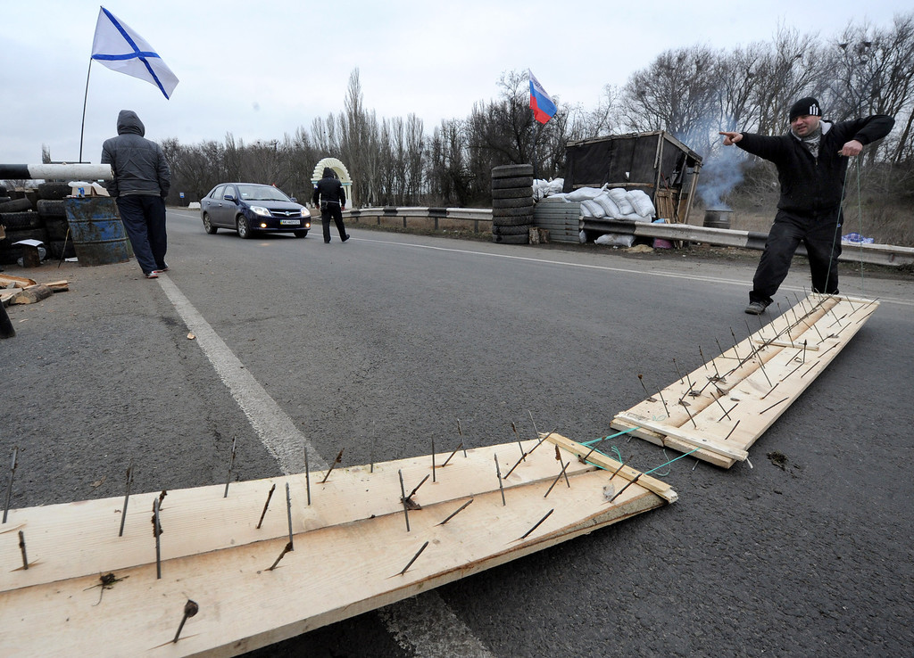 . One of the  men who called themselves members of local militia used makeshift road spike barriers to block a highway that connect Black Sea Crimea peninsula to mainland Ukraine at their checkpoint near the city of Armyansk, on February 28, 2014.  AFP PHOTO / VIKTOR DRACHEV/AFP/Getty Images