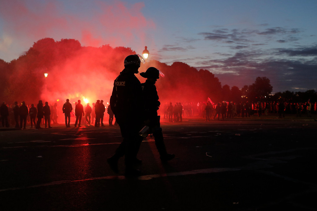 . Anti-gay marriage demonstrators face riot police while flares smoke during clashes in Paris, France, Sunday, May 26, 2013. Tens of thousands of people protested against France\'s new gay marriage law in central Paris on Sunday. The law came into force over a week ago, but organizers decided to go ahead with the long-planned demonstration to show their continued opposition as well as their frustration with President Francois Hollande, who had made legalizing gay marriage one of his keynote campaign pledges in last year\'s election.(AP Photo/Laurent Cipriani)