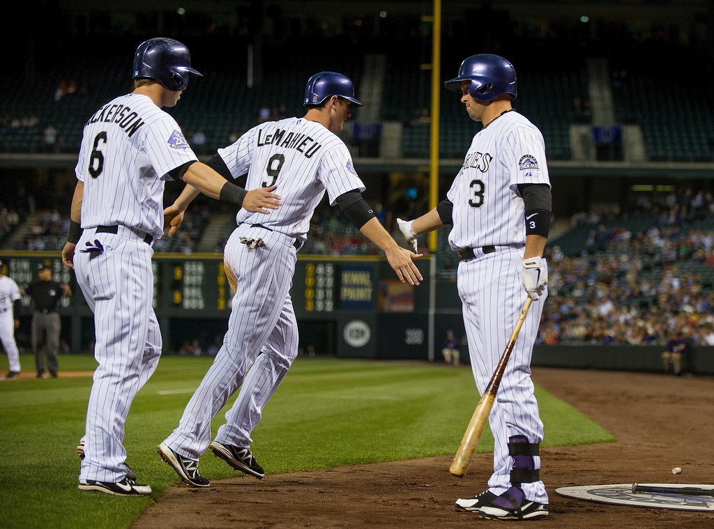 . DJ LeMahieu #9, Corey Dickerson #6 and Michael Cuddyer #3 of the Colorado Rockies celebrate a pair of first inning runs on a single by Troy Tulowitzki #2 (not pictured) against the St. Louis Cardinals at Coors Field on September 18, 2013 in Denver, Colorado. (Photo by Dustin Bradford/Getty Images)