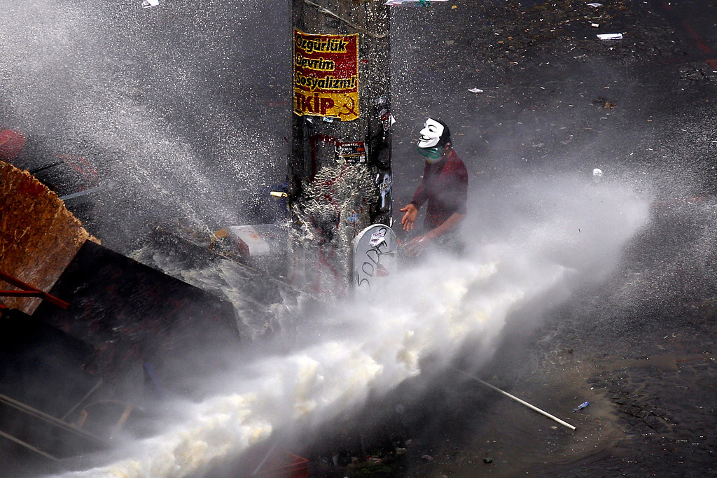 . A protester tries protect from water projected by a water canon from police during clashes in Taksim square in Istanbul, Tuesday, June 11, 2013.  (AP Photo/Kostas Tsironis)