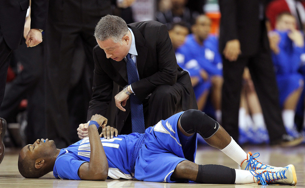. Air Force head coach Dave Pilipovich tends to Michael Lyons on the court after Lyons was hurt in the first half of a Mountain West Conference tournament NCAA college basketball game against UNLV, Wednesday, March 13, 2013, in Las Vegas. (AP Photo/Isaac Brekken)
