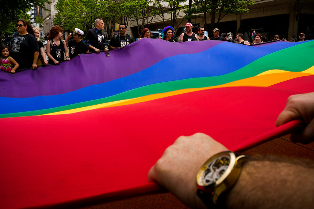 ". Marchers stretch out a large pride flag across the street during the 40th annual Seattle Pride Parade Sunday, June 29, 2014, in Seattle, Wash. This year\'s theme was ìGenerations of Pride."" (AP Photo/seattlepi.com, Jordan Stead)"