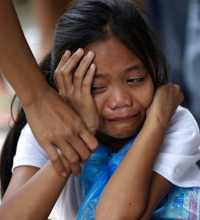 . A girl is comforted upon seeing the sealed coffin of her relative at a damaged public market which now serves as a makeshift mortuary for typhoon Bopha\'s victims at New Bataan township, Compostela Valley in southern Philippines Saturday Dec. 8, 2012. Search and rescue operations following typhoon Bopha that killed nearly 600 people in the southern Philippines have been hampered in part because many residents of this ravaged farming community are too stunned to assist recovery efforts, an official said Saturday. (AP Photo/Bullit Marquez)