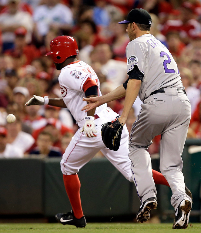 . Colorado Rockies starting pitcher Jon Garland, right, tosses the ball to first for the out after fielding a bunt by Cincinnati Reds\' Derrick Robinson, left, in the fifth inning of a baseball game on Wednesday, June 5, 2013, in Cincinnati. (AP Photo/Al Behrman)