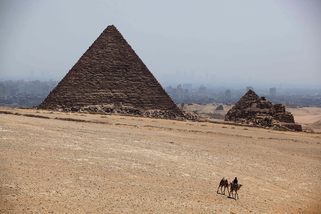 . A man rides a camel past Khufu pyramid, the largest of pyramids at the historical site of the Giza Pyramids, near Cairo, Egypt, Tuesday, Aug. 27, 2013. Tourism in Egypt has dropped following unrest surrounding the July 3 popularly backed military coup that ousted President Mohammed Morsi. (AP Photo/Jon Gambrell)