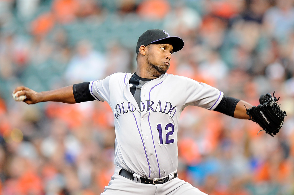 . BALTIMORE, MD - AUGUST 16:  Juan Nicasio #12 of the Colorado Rockies pitches in the second inning against the Baltimore Orioles at Oriole Park at Camden Yards on August 16, 2013 in Baltimore, Maryland.  (Photo by Greg Fiume/Getty Images)