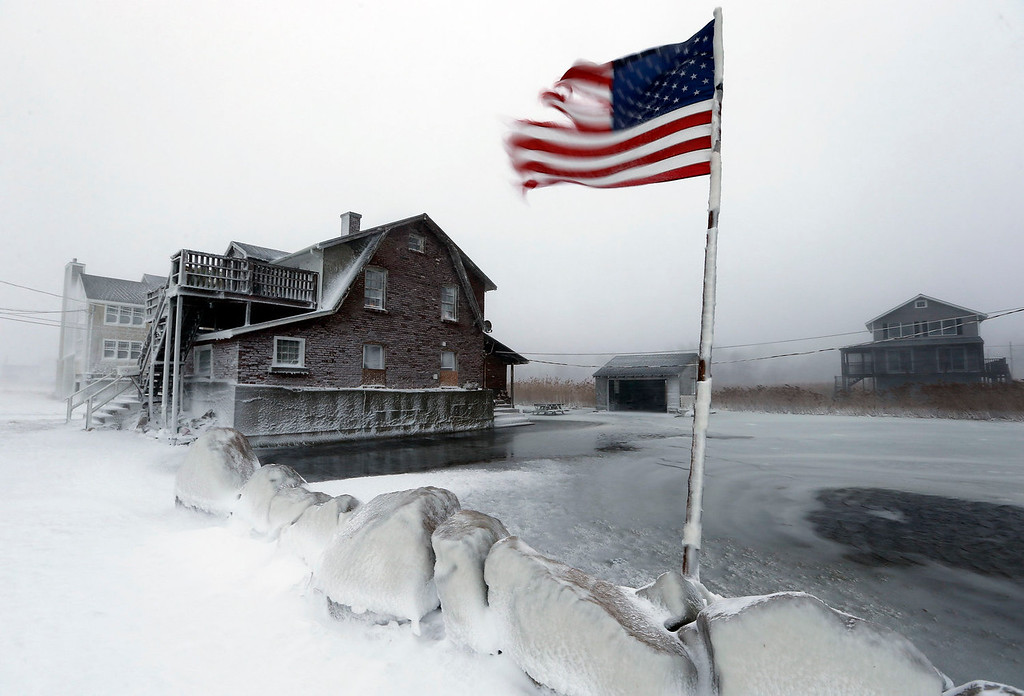 . A tattered flag flies by a flooded yard along the shore in Scituate, Mass., Friday, Jan. 3, 2014. A blustering winter storm that dropped nearly 2 feet of snow just north of Boston, shut down major highways in New York and Pennsylvania and forced U.S. airlines to cancel thousands of flights nationwide menaced the Northeast on Friday with howling winds and frigid temperatures. (AP Photo/Michael Dwyer)
