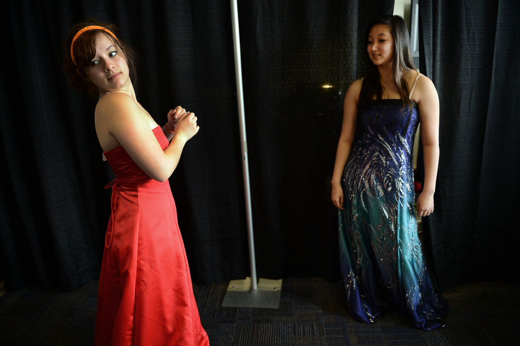 ". COMMERCE CITY, CO. - MARCH 16:  Raven Gereaux, left, and Allison Okita, both seniors at Legacy High School, try on dresses during the Prom Dress Exchange Corp. event in Commerce City, CO March 16, 2013. With a valid student ID and a suggested $10 donation, teenage girls could chose from 1,356 donated dresses that lined a long hallway at Dick�s Sporting Goods Park. Gereaux said, ""prom is so expensive already, I think it\'s a great opportunity for girls to get a really nice dress for a reasonable price.\"" (Photo By Craig F. Walker/The Denver Post)"