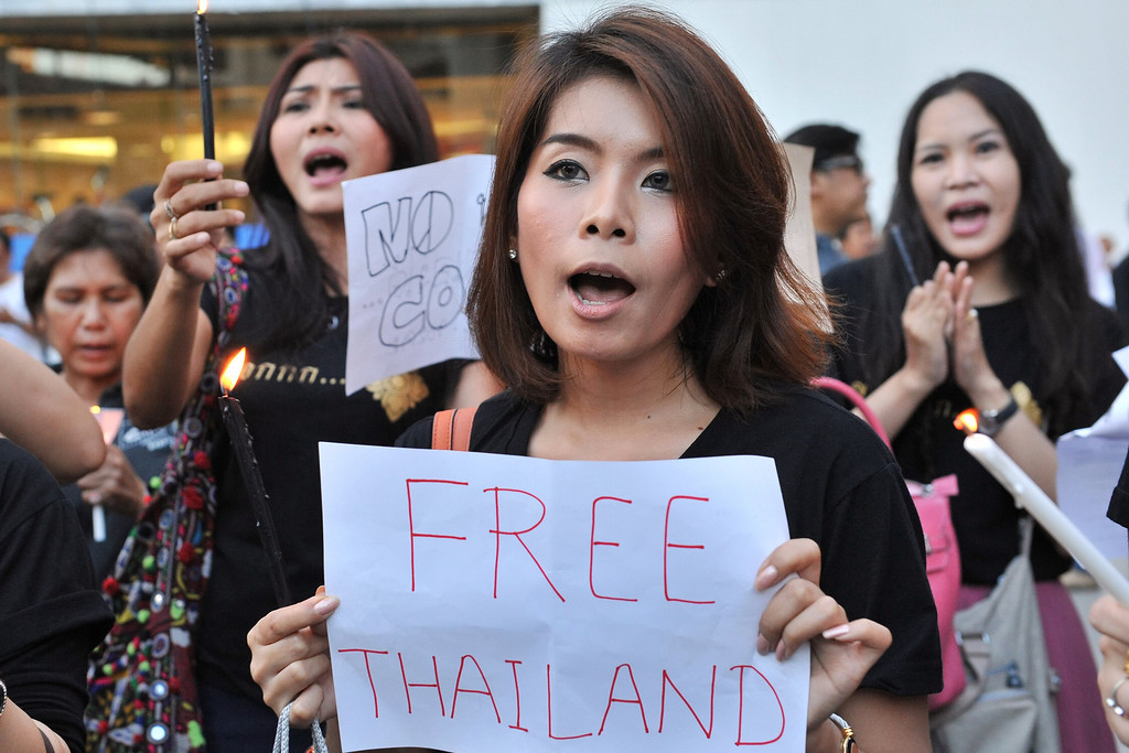 . Protesters sing during an anti-coup rally on May 23, 2014 in Bangkok, Thailand. Anti-coup protesters rallied in Bangkok\'s shopping district, a day after the military seized control in a bloodless coup. (Photo by Rufus Cox/Getty Images)