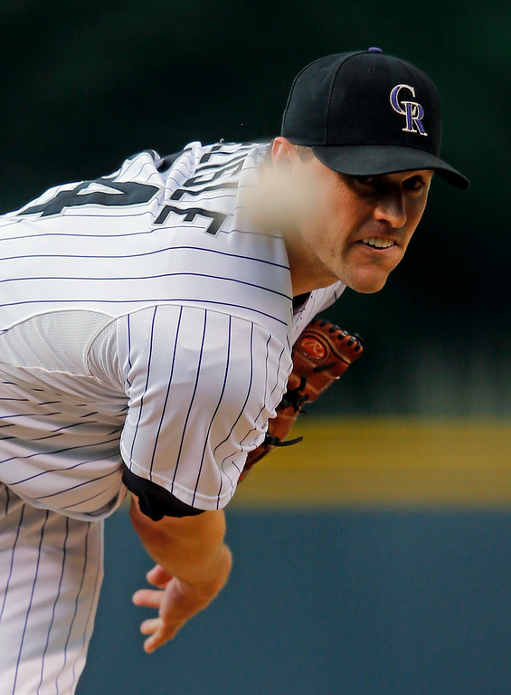 . Colorado Rockies starting pitcher Matt Belisle throws to a Cincinnati Reds batter during the first inning of a baseball game Friday, Aug. 15, 2014, in Denver. (AP Photo/Jack Dempsey)