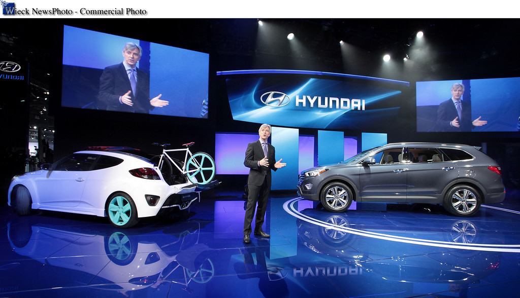 . Los Angeles - November 28, 2012 - Los Angeles - Nov. 28, 2012 - Hyundai Motor America President and CEO John Krafcik, today introduced the all-new seven-passenger Santa Fe, right, and Veloster Roll Top C3 Concept at the 2012 Los Angeles Auto Show. This marks the world debut of the latest version of the popular family crossover that includes the two-row, five-passenger Santa Fe Sport trim level, which has been on sale since August. The all-new Santa Fe family showcases Hyundai\'s cutting-edge capabilities through precise design, high-output powertrains with Gasoline Direct Injection (GDI) and a host of features to please drivers and passengers with high expectations for functionality, versatility and comfort. Veloster Roll Top C3 Concept (which stands for Convertible 3-door) combines open-air freedom with the style of a coupe and the functionality of a tailgate. The Veloster\'s efficient coupe design with hidden passenger-side third door introduces an innovative dual-function roll top and tailgate, adding unique utility to a convertible. (Joe Wilssens photo)