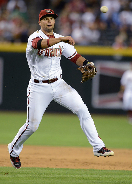 . Martin Prado #14 of the Arizona Diamondbacks makes a running throw to first base in the third inning against the Colorado Rockies at Chase Field on April 28, 2014 in Phoenix, Arizona.  (Photo by Norm Hall/Getty Images)
