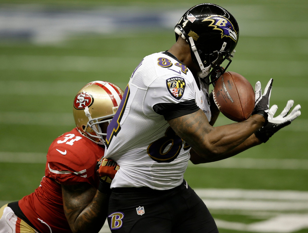 . Baltimore Ravens tight end Ed Dickson (84) makes a catch against San Francisco 49ers safety Donte Whitner (31) during the first half of NFL Super Bowl XLVII football game, Sunday, Feb. 3, 2013, in New Orleans. (AP Photo/Elaine Thompson)
