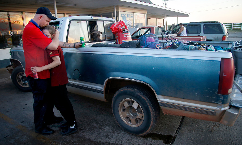 . Alyssa Hutton and Jesse Cannon embrace in front of their truck with items they were able to gather before evacuating from a wildfire zone in Logan County, Okla., Sunday, May 4, 2014. About 1,000 people were evacuated from homes in the city about 35 miles north of Oklahoma City Sunday, according to the Guthrie Fire Department.  Firefighters worked through the night and into early Monday to battle the large wildfire that destroyed at least six homes and left at least one person dead after a controlled burn spread out of control in central Oklahoma. (AP Photo/The Oklahoman, Sarah Phipps)